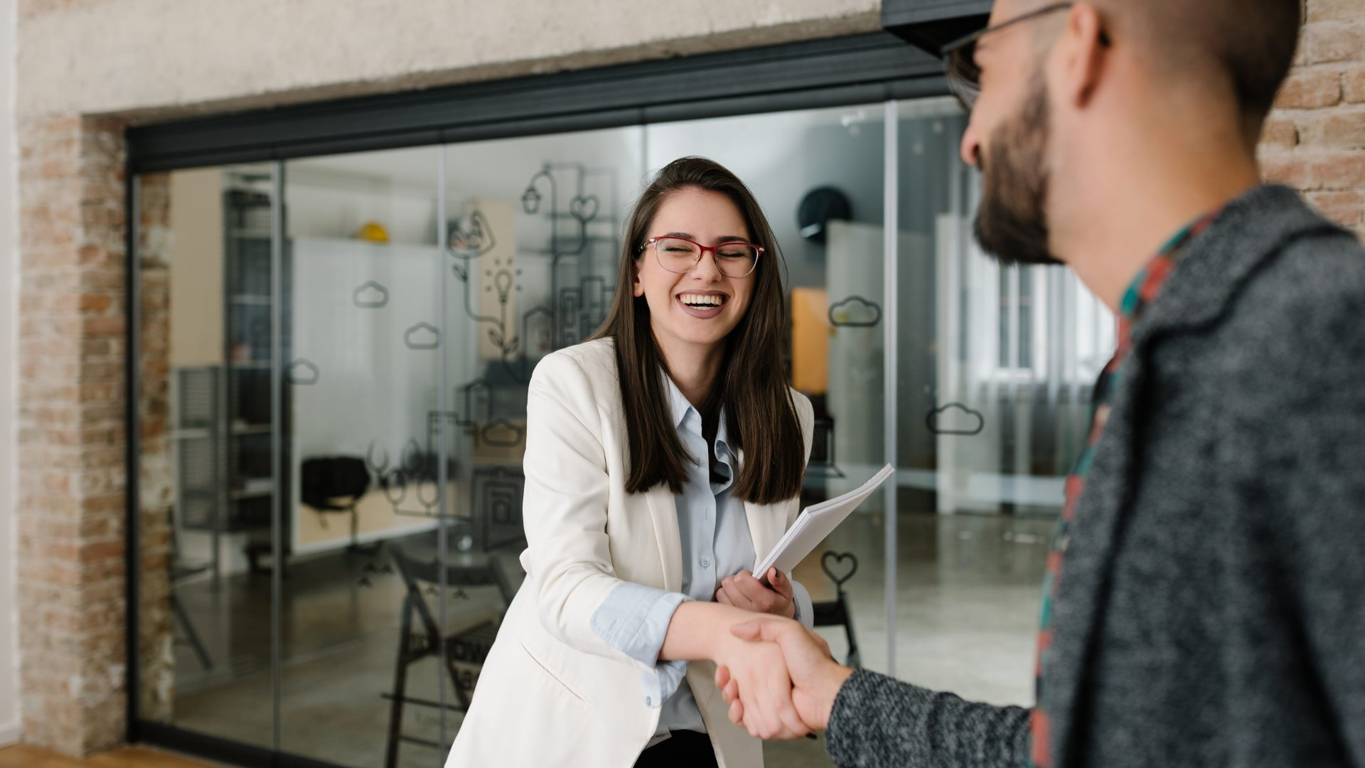 Woman smiling and shaking hands during her values-based recruiting interview